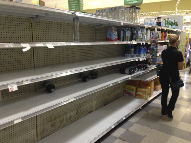 A shopper walks by the empty shelves where bottled water normally would be, Wednesday, Oct. 5, 2016, at a grocery store in Hollywood, Fla. Hurricane Matthew marched toward Florida, Georgia and the Carolinas and nearly 2 million people along the coast were urged to evacuate their homes Wednesday, a mass exodus ahead of a major storm packing power the U.S. hasn't seen in more than a decade. (AP Photo/Wilfredo Lee)