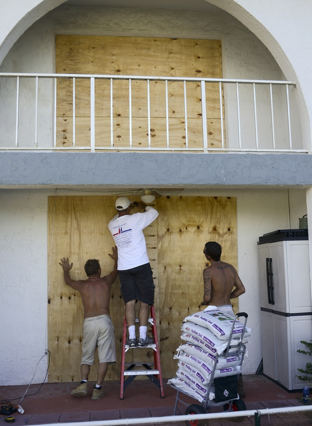 Paul Grimes, Lawrence Tanner and Ricky Corliss help board up apartments in advance of Hurricane Matthew on Wavecrest Avenue in Melbourne Beach, Fla., Wednesday, Oct. 5, 2016. The building is just over the dune line from the Atlantic. Most of the counties along Florida's Atlantic coast have issued mandatory evacuations along the eastern most areas. (Craig Bailey/Florida Today via AP)