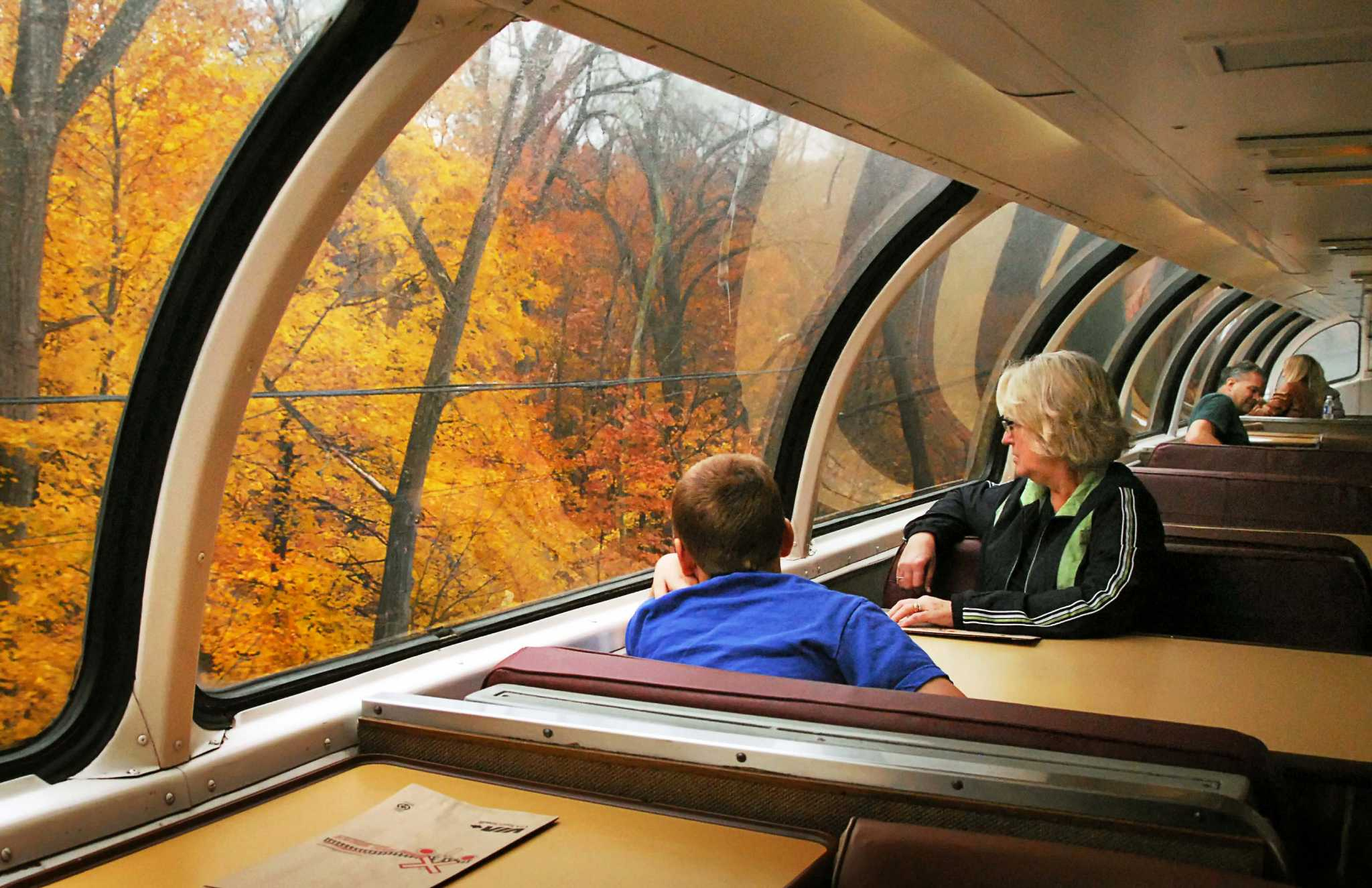"Passengers look at fall foliage as they ride the historic ""Great Dome Car,"" on Amtrak's Adirondack service between Albany and Montreal."